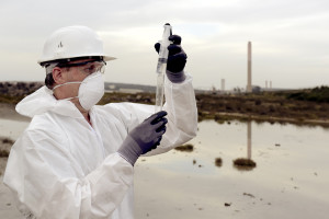 Insured worker in a protective suit examining pollution in the water at the industry.